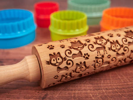 Embossed rolling pin with a cat pattern and some colorful cookie cutters, on wood background 免版税图像 - 152390991