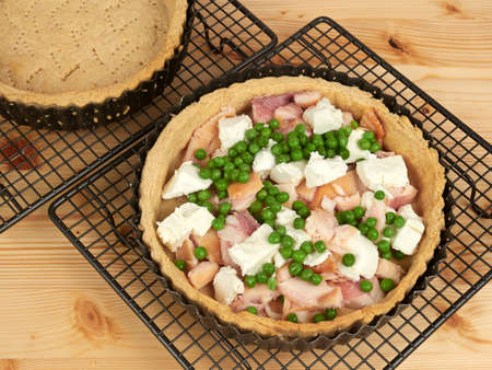 Making a quiche with smoked trout, goat cheese and green peas 免版税图像 - 153284686