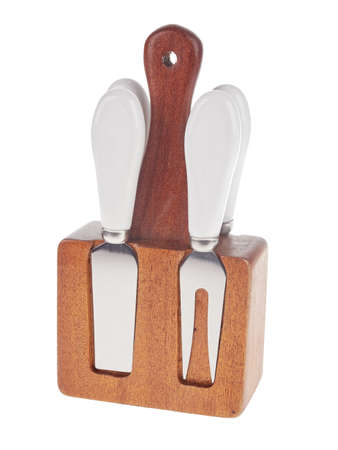 Set of stainless steel cheese cutlery, with white handles and wooden block, isolated on white background 免版税图像