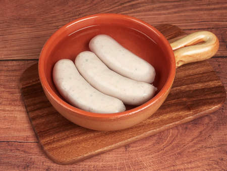 Traditional Bavarian white sausages (weisswurst) on a wooden board 免版税图像