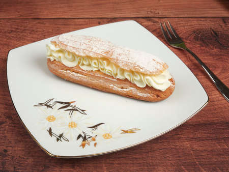 Traditional french eclair with whipped cream, on a white plate, on brown wooden background 免版税图像