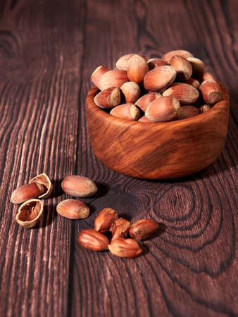 Hazelnuts in an olive wood bowl, on brown wood background