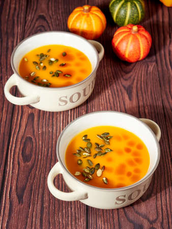 Two bowls of homemade pumpkin soup, decorated with pumpkin seeds and drops of pumpkin oil, on brown background