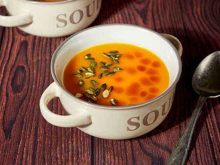 Two bowls of homemade pumpkin soup, decorated with pumpkin seeds and drops of pumpkin oil, on brown background 免版税图像 - 156094546