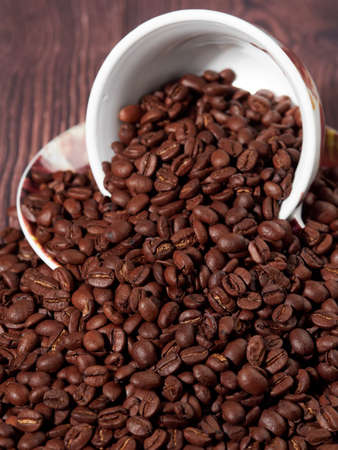 Coffee beans in a cappuccino cup, on brown background 免版税图像
