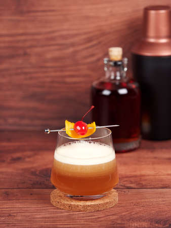 Amaretto sour: a cocktail made with amaretto liqueur, lemon juice, simple syrup and egg white, and topped with a cherry and orange 免版税图像 - 157025443