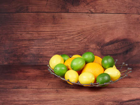 A basket of citrus fruits: limes, lemons and oranges