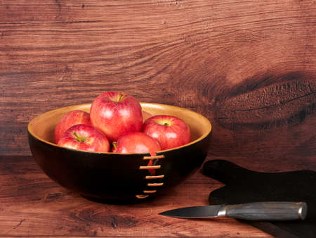 Red apples in a dark brown bowl, on wooden backdrop 免版税图像 - 157025458