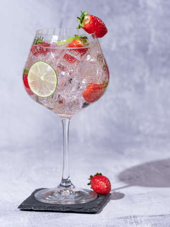 Strawberry gin decorated with a fresh strawberries and slices of lime 免版税图像