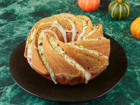 Homemade pumpkin bundt cake drizzled with an orange glaze and sprinkled with chopped pistachios