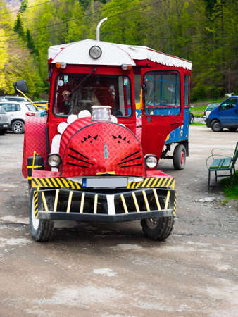 Busteni, Romania - May 3, 2014: A red tractor with a trailer acts as a means of transportation between Busteni Train Station and Gura Diham chalet
