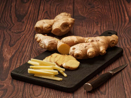 Ginger root cut into strips and slices on a burned wood cutting board over a brown wood background, selective focus 免版税图像