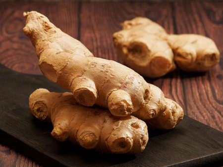 Ginger root on a burned wood cutting board over brown wood background