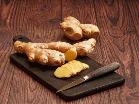 Ginger root, slices of ginger root and a knife on a burned wood cutting board over brown wood background