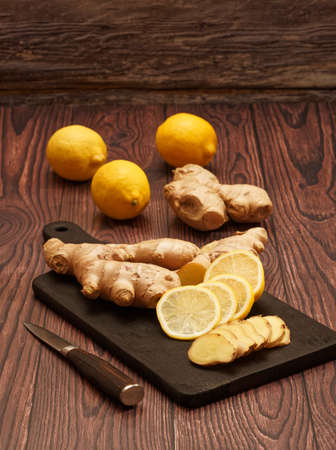 Ginger root, slices of ginger root and slices of lemon on a burned wood cutting board over brown wood background 免版税图像