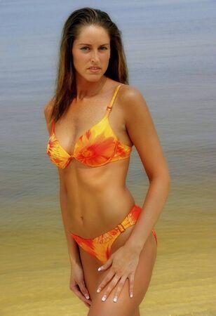 Young woman wearing a bikini standing on the beach photo