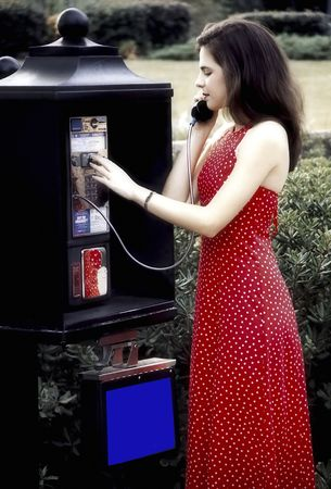19's: Young attractive woman talking on a pay phone outdoors Stock Photo