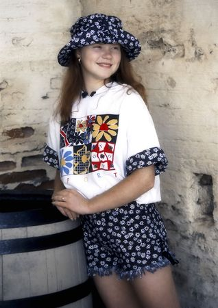 Young teenage girl in a casual summer outfit wearing a hat photo