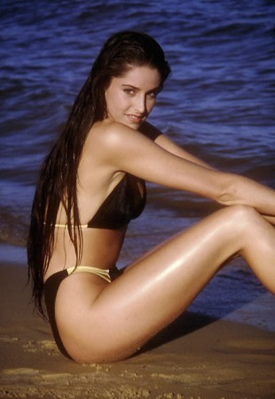 A sexy woman sitting and posing in a black and gold bikini photo