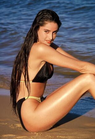 Young attractive woman sitting on the beach wearing a black and golden bikini photo