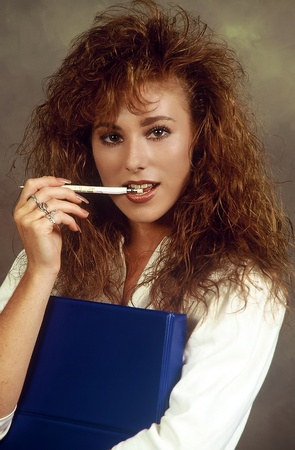 Young business woman holding a notebook with a pencil in her mouth photo