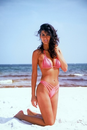 Young attractive woman posing in a pink bikini photo