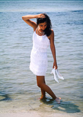 Attractive young woman standing barefoot in the water holding her shoes photo