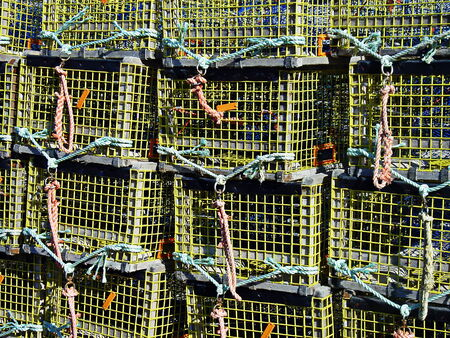 lobster pot: Lobster traps stacked in the harbor of Lower West Pubnico, Nova Scotia, Canada Stock Photo