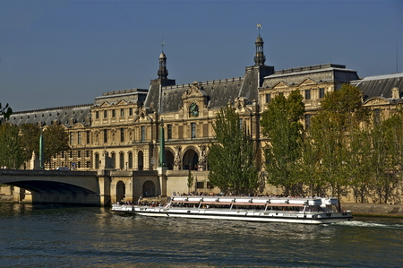 carrousel: A tour boat on the Seine in Paris. A view of Pont du Carrousel and guichets du Louvre can be seen in the background