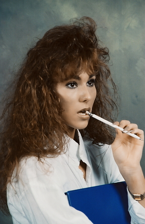 ttractive: Close-up of an ttractive female with a pen in her mouth holding a blue binder Stock Photo