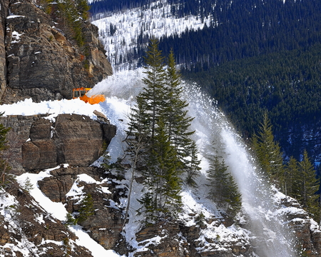A snow plow working on clearing a Colorado highway