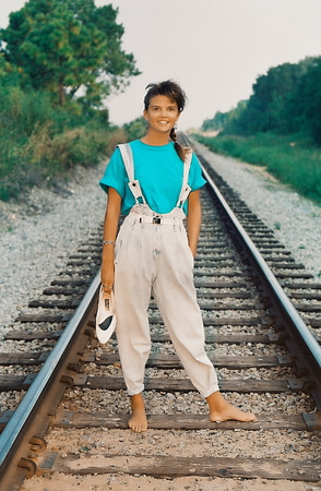 Young female standing on railroad tracks