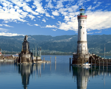 Lindau's famous harbor entrance on the eastern side of Lake Constance (Bodensee) with the lighthouse and iconic Bavarian lion sculpture in the foreground - Lindau, Germany
