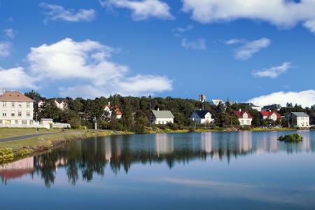 Houses and buildings reflected in lake Tjornin in Reykjavik Iceland Standard-Bild - 115064664