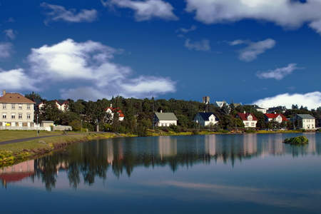 Houses and buildings reflected in lake Tjornin in Reykjavik Iceland Standard-Bild - 115064672