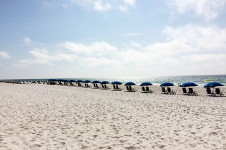 Beach umbrellas lining the white sand on Pensacola Beach, Florida Standard-Bild - 117353178