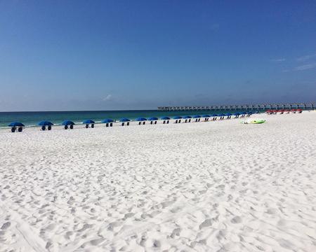 Beach umbrellas lining the white sand on Pensacola Beach, Florida