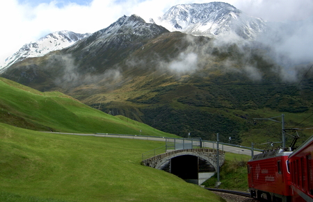 Glacier Express with a view of the Oberalpstrasse between Andermatt / Oberalpsee, Switzerland Standard-Bild - 117353684