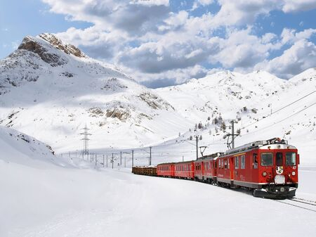 The Bernina Express traveling between Lagalb and Ospizio Bernina can be seen passing the snow-covered Lej Pitschen