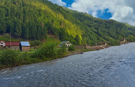Vaser River flowing past houses in the town of Vișeu de Sus, Maramures County, Maramures, Romania