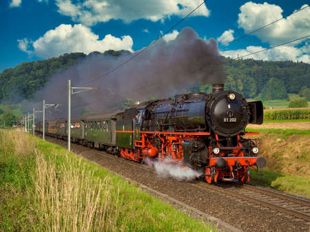 A German steam locomotive with passenger cars traveling through the Swiss countryside. Standard-Bild