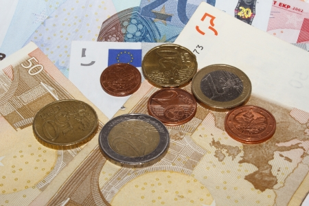 five cents: Different euro coins on various euro notes