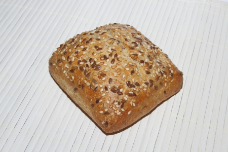 Whole wheat bun - on rustic background photo