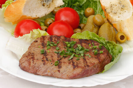 Grilled beef steak served on a plate with salad and vegetables
