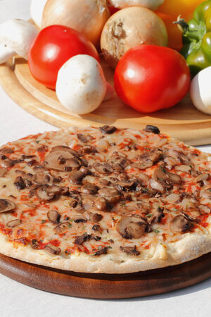 Pizza with mushrooms and cheese on a wooden plate Stock Photo