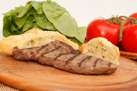 Grilled beef steak served on a wooden cutting board with salad and vegetables