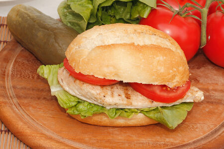 Chicken with Salad and tomato in a bun photo