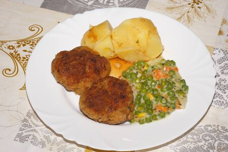 Meatballs with potatoes and peas on a plate photo