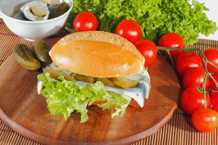 Fish rolls with sour herring, pickled herring, garnished with lettuce, tomato and pickles on a wooden board Stock Photo