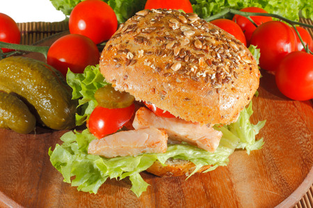 Whole wheat bread with fried fillet of chicken, garnished with pickled cucumbers, tomatoes and lettuce on a wooden board Stock Photo